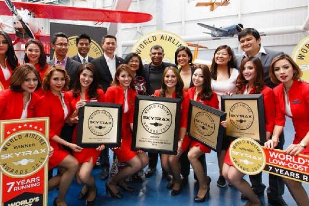 KERJASAMA ERAT: Tan Sri Tony Fernandes (tengah) bersama pihak pengurusan dan kakitangan AirAsia dan AirAsiaX bergambar sama selepas menerima anugerah Skytrax yang baru lalu. - Foto AIRASIA