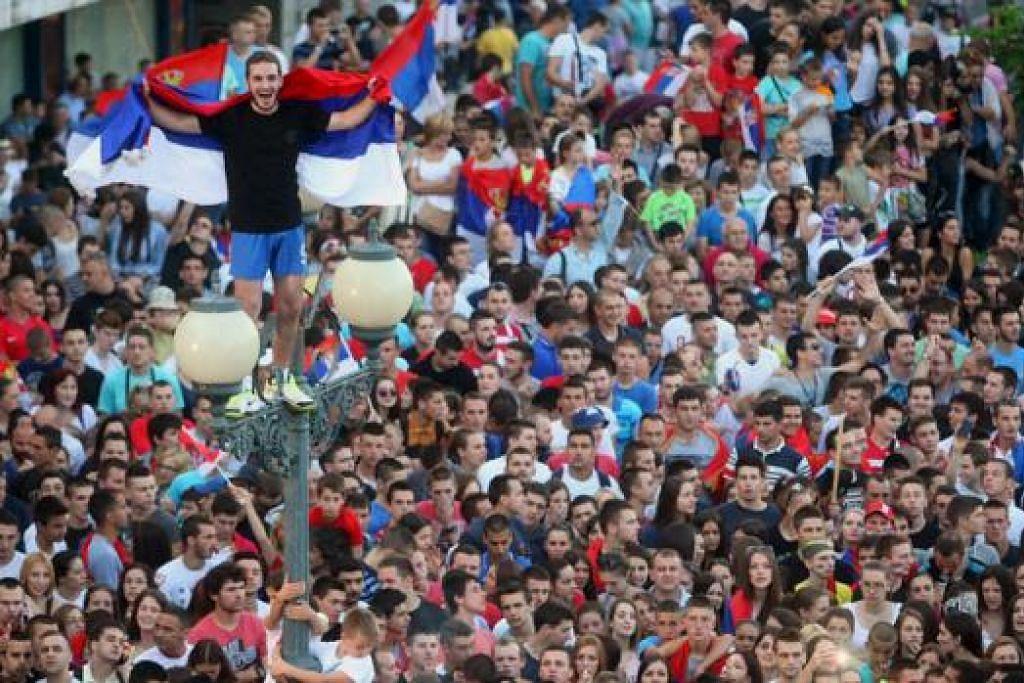 JUARA DUNIA: Para pemain Skuad Bawah 20 Tahun Serbia menunjukkan piala yang mereka menangi kepada para peminat di Belgrade. Mereka telah disambut sekitar 50,000 penyokong (gambar atas), yang ingin sama-sama meraikan kejayaan pasukan itu menjadi juara selepas mengalahkan Brazil. - Foto REUTERS