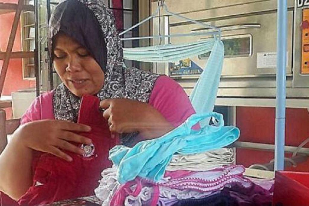 TIDAK DAPAT TAHAN SEBAK: Cik Zaini Daud tidak dapat menahan kesedihan sambil memegang baju Raya anaknya, Nur Aminah Zaimin Jasmin, yang maut dilanggar kenderaan yang dipandunya. - Foto UTUSAN MALAYSIA