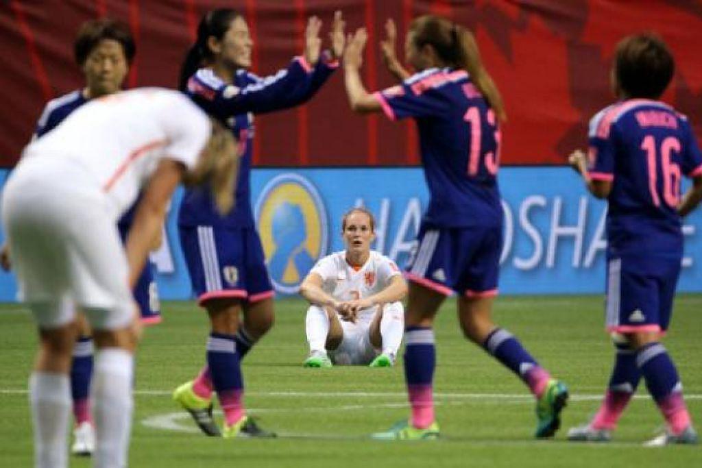 WAJAH GEMBIRA DAN LUKA: Para pemain Jepun (jersi biru) meraikan kejayaan melangkah ke suku akhir Piala Dunia Wanita sedang pemain Belanda, Desiree Van Lunteren (tengah), terduduk kecewa. - Foto REUTERS