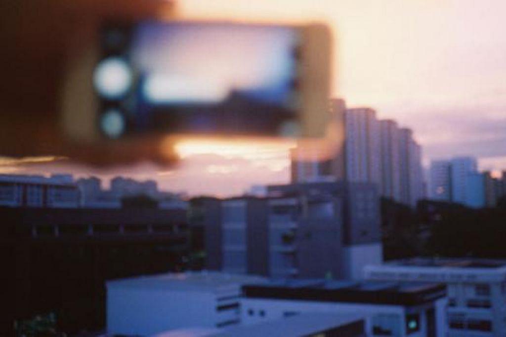 SENJA: Pelajar Muhammad Asnur cuba merakamkan pemandangan matahari terbenam dari kawasan perumahan Lengkok Bahru. - Foto KOPITIAM LENGKOK BAHRU