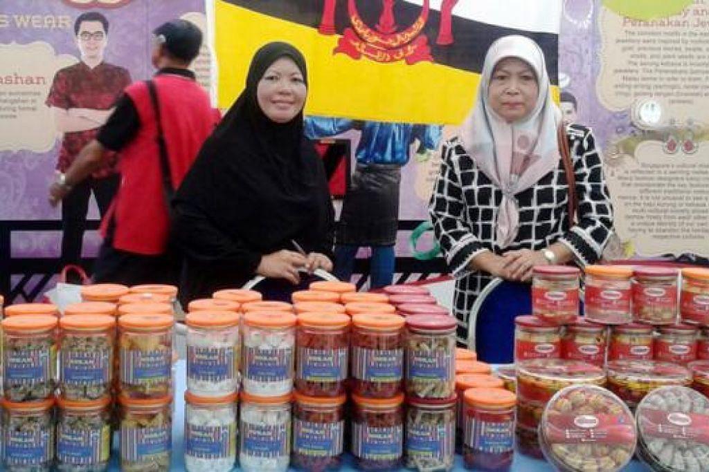 BERKONGSI BUDAYA BRUNEI: Hajjah Kamariah Hasbullah (kanan) bersama kakitangan syarikatnya menjual kuih-muih di gerai Brunei di bazar Ramadan Tampines untuk memberi pelanggan peluang menikmati rasa asli Brunei. - Foto ROZAIMEE ABDULLAH