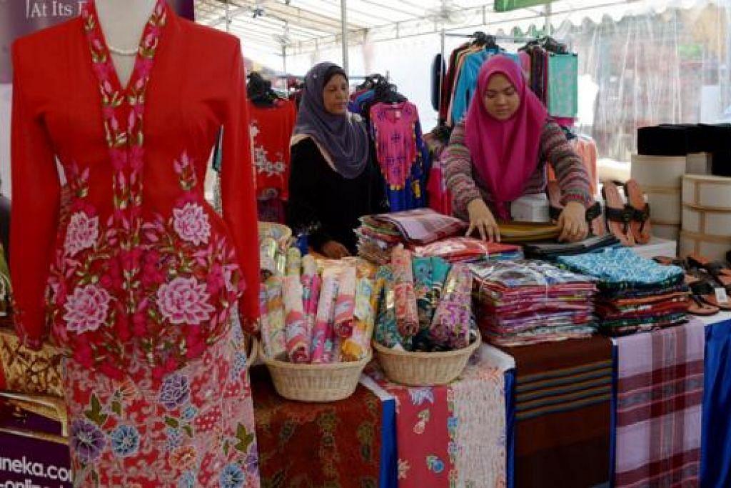 MALAYSIA BOLEH: Cik Aliah Abdullah (kanan) dan Cik Nur Hayati Mat Zaini sibuk mempamerkan pakaian tradisi Malaysia untuk pelanggan. - Foto TUKIMAN WARJI
