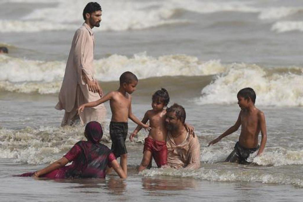 DINGINKAN BADAN: Sekumpulan penduduk Karachi di pantai untuk melarikan diri daripada cuaca panas yang mencengkam Pakistan itu dan telah menyebabkan lebih 600 orang terkorban. - Foto AFP