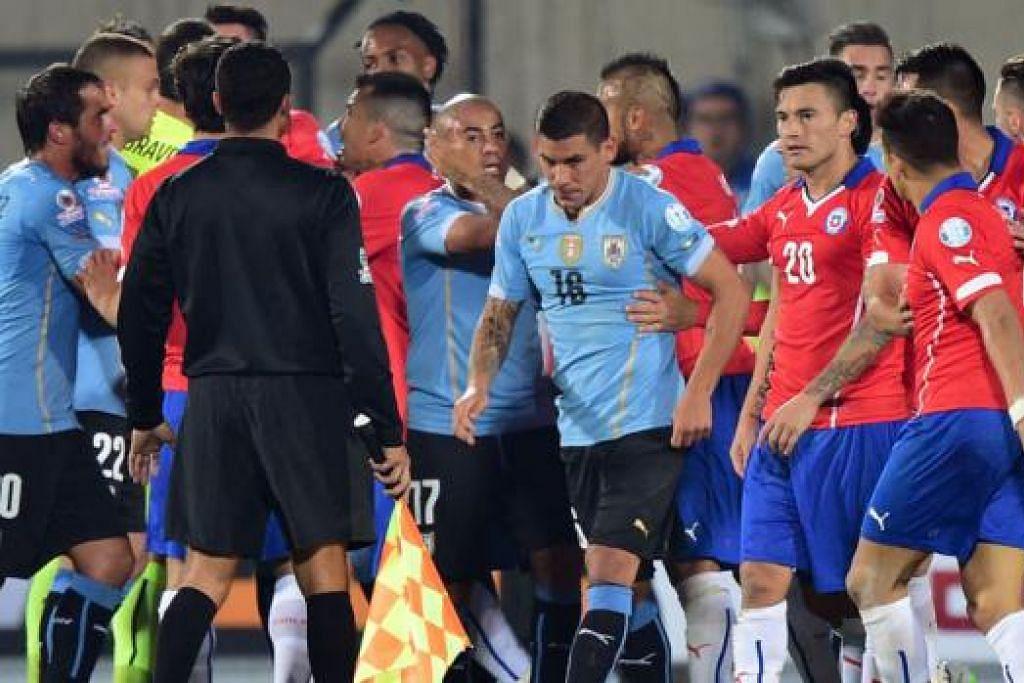 GADUH: Pemain Chile (berjersi merah) dan Uruguay (berjersi biru) tolak-menolak dan bergaduh pada lewat perlawanan suku akhir mereka dalam kejohanan Piala Amerika. - Foto AFP