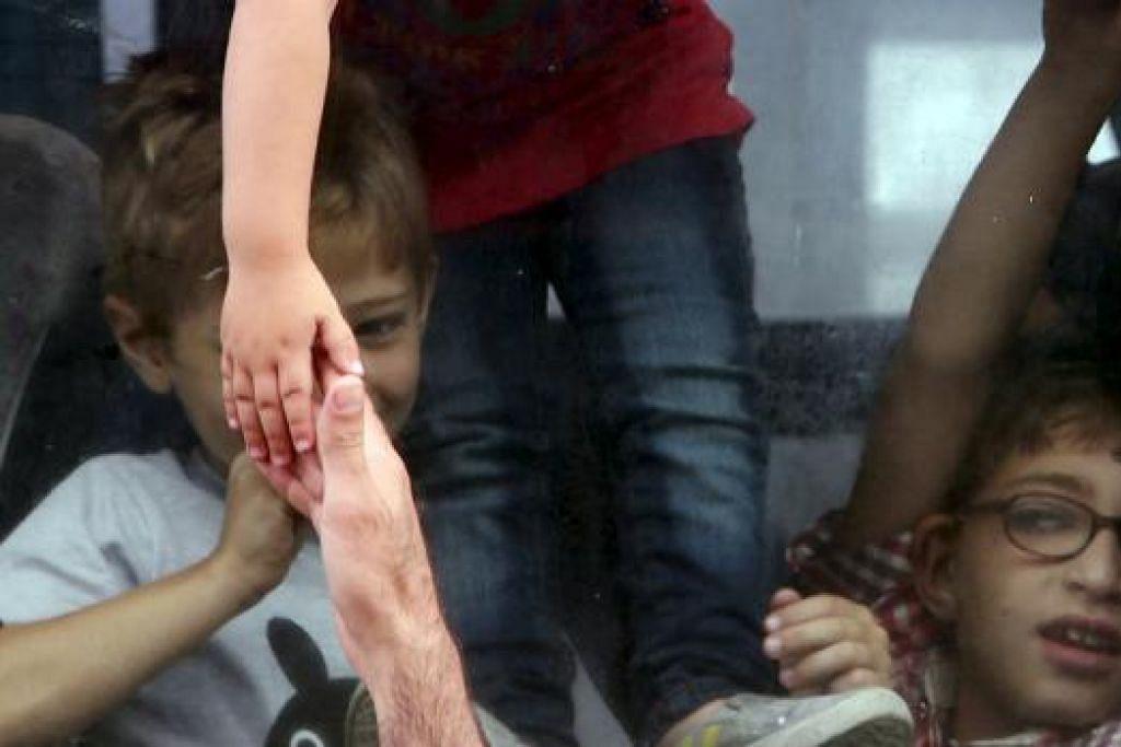 SELAMAT JALAN: Seorang gadis Palestin menyentuh tangan saudaranya (bawah) sebelum menaiki kereta api masuk ke Mesir melalui pintu masuk Rafah baru-baru ini. Mesir telah membuka sempadannya kepada rakyat Palestin selama tiga hari untuk membenarkan rakyat Palestin keluar masuk Jaluran Gaza. - Foto REUTERS