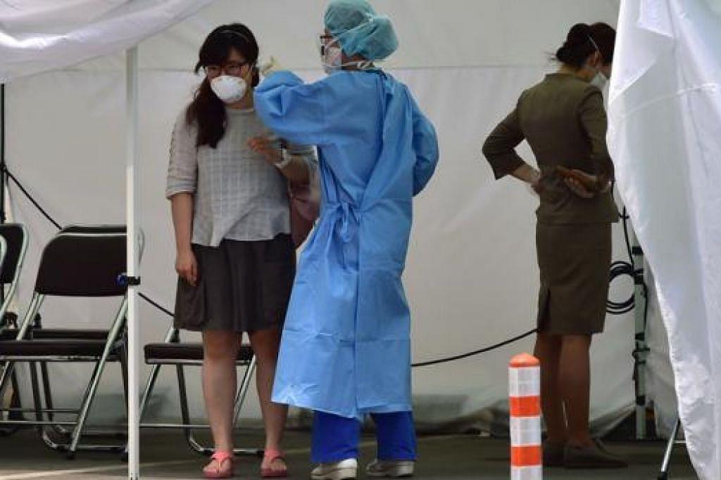 CUBA KEKANG VIRUS: Seorang kakitangan perubatan berpakaian keselamatan memeriksa suhu badan seorang pelawat di Hospital Konkuk Universiti di Seoul sebagai langkah berjaga-jaga. - Foto AFP