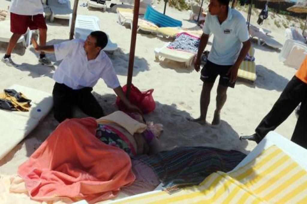 BERI BANTUAN: Lelaki warga Tunisia membantu seorang wanita yang cedera di bandar peranginan Sousse, 140 kilometer ke selatan ibukota Tunisia. Hampir 40 orang, sebilangan besar pelancong asing, terbunuh dalam serangan di pantai peranginan yang dipenuhi dengan pelancong yang sedang bercuti. - Foto AFP