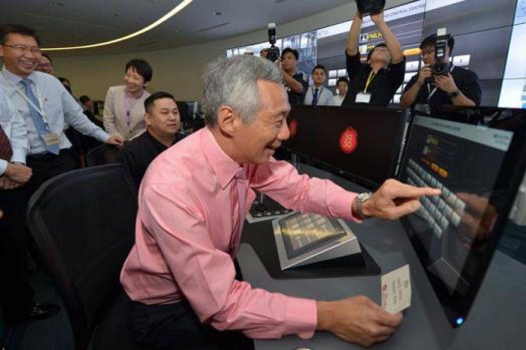 PELABUHAN CANGGIH: Encik Lee mendapat peluang mengendali kren dari Pusat Operasi Kren Automatik selepas pelancaran Fasa 3 dan 4 Terminal Pasir Panjang. - Foto THE STRAITS TIMES
