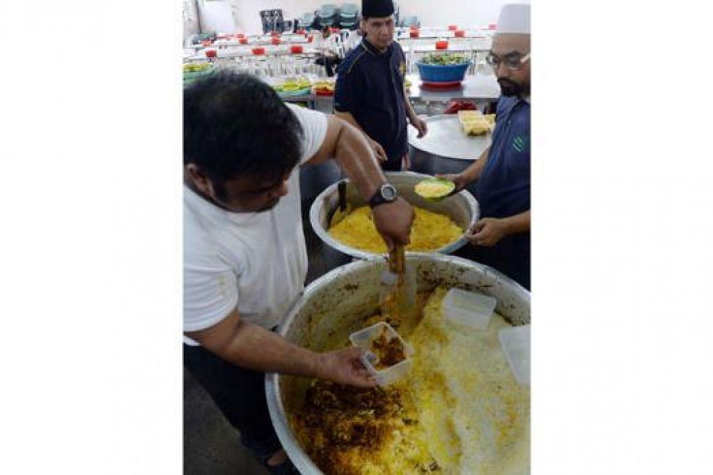 BERBUKA DENGAN BERIANI: Relawan, Encik Abdul Hakeem Sulaiman (berbaju putih), memasak nasi beriani lalu membungkuskannya agar jemaah boleh bawa pulang sebagai hidangan sahur esok pagi.