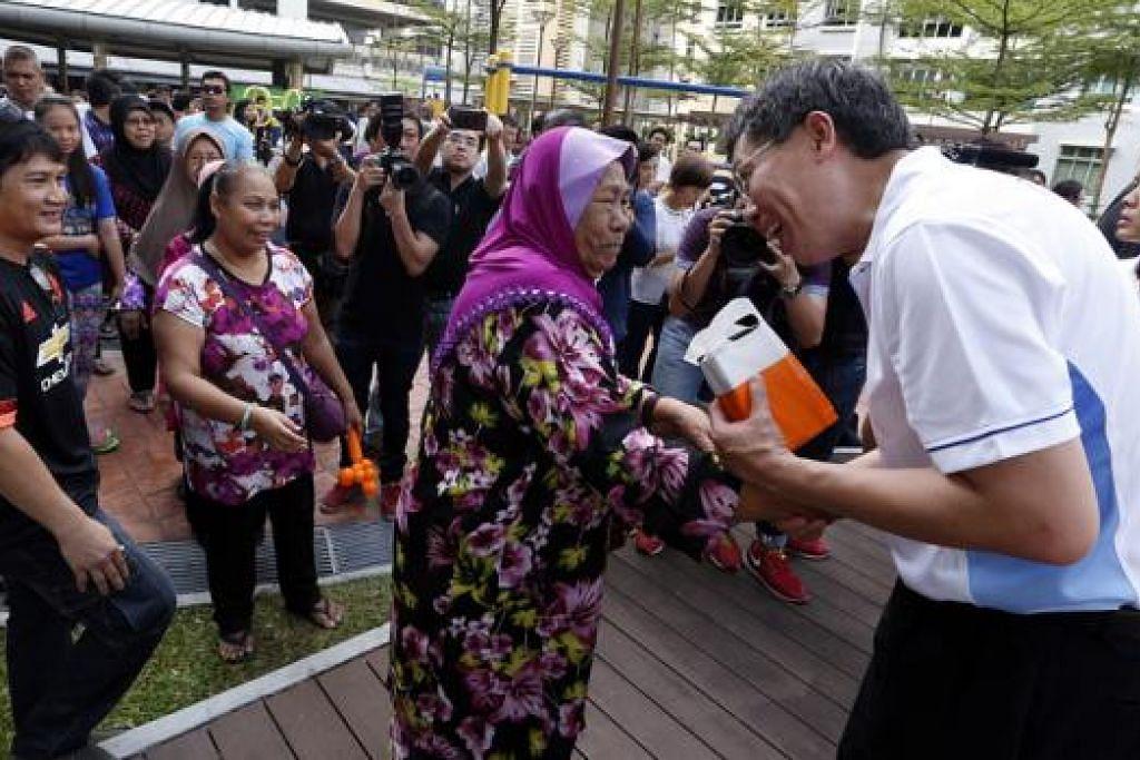 BERAMAH DENGAN PENDUDUK: Encik Lui berinteraksi dengan penduduk dan pemilik kedai semasa melawat Zhenghua semalam. - Foto THE STRAITS TIMES