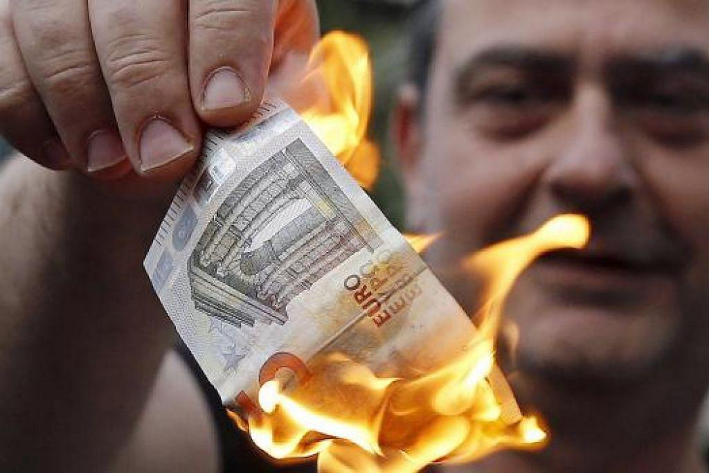 Krisis semakin membara: Seorang penunjuk perasaan membakar matawang euro di Athens, Greece.