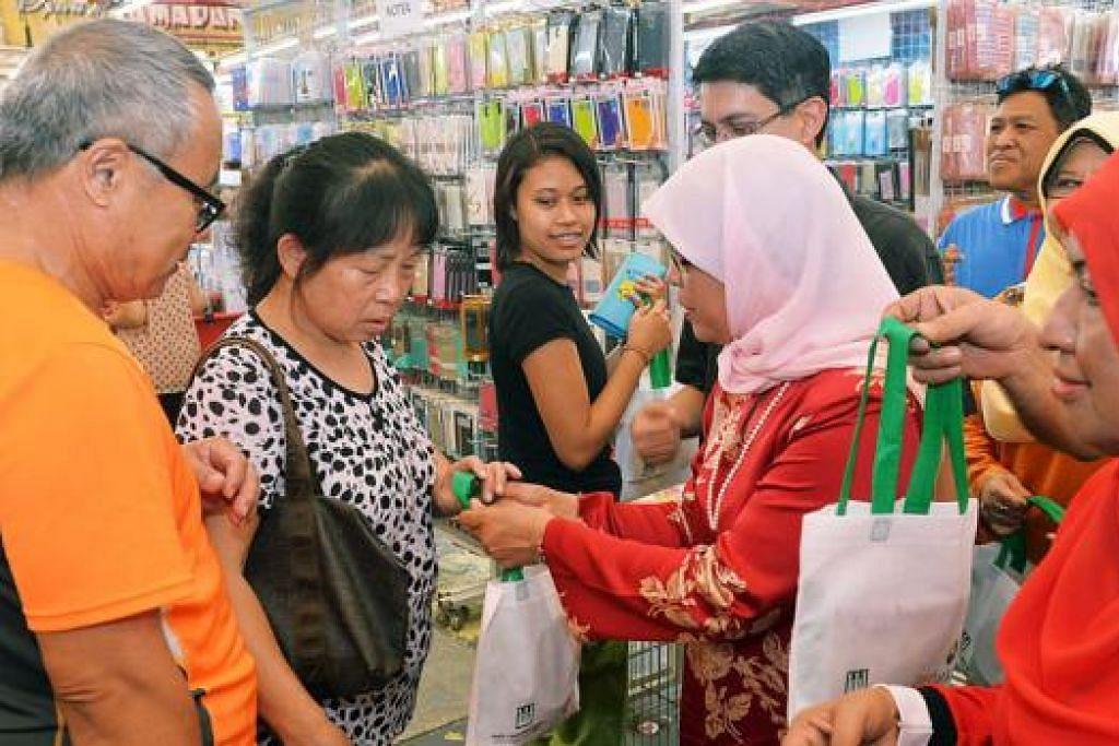 BERKONGSI MAKLUMAT: Cik Halimah (tudung merah jambu) dan Profesor Madya Faishal (di belakangnya) memberikan beg berisi maklumat Pakej Generasi Perintis dan MediShield Hayat kepada pengunjung di Bazar Raya Utama di Woodlands petang semalam. - Foto KHALID BABA