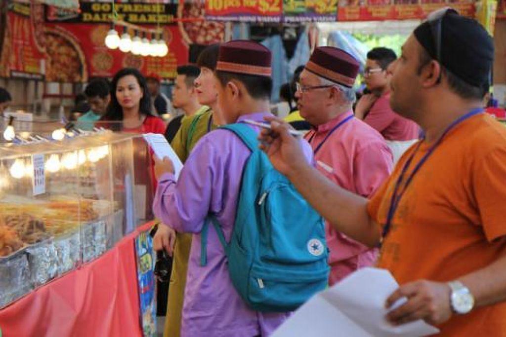 TANGKAS BERESKAN TUGASAN: Peserta Perlumbaan Penerokaan Budaya perlu selesaikan tugasan atau cabaran yang diberi sepanjang menjelajah gerai Bazar Geylang Serai. - Foto JAWATANKUASA PENYALAAN LAMPU HARI RAYA