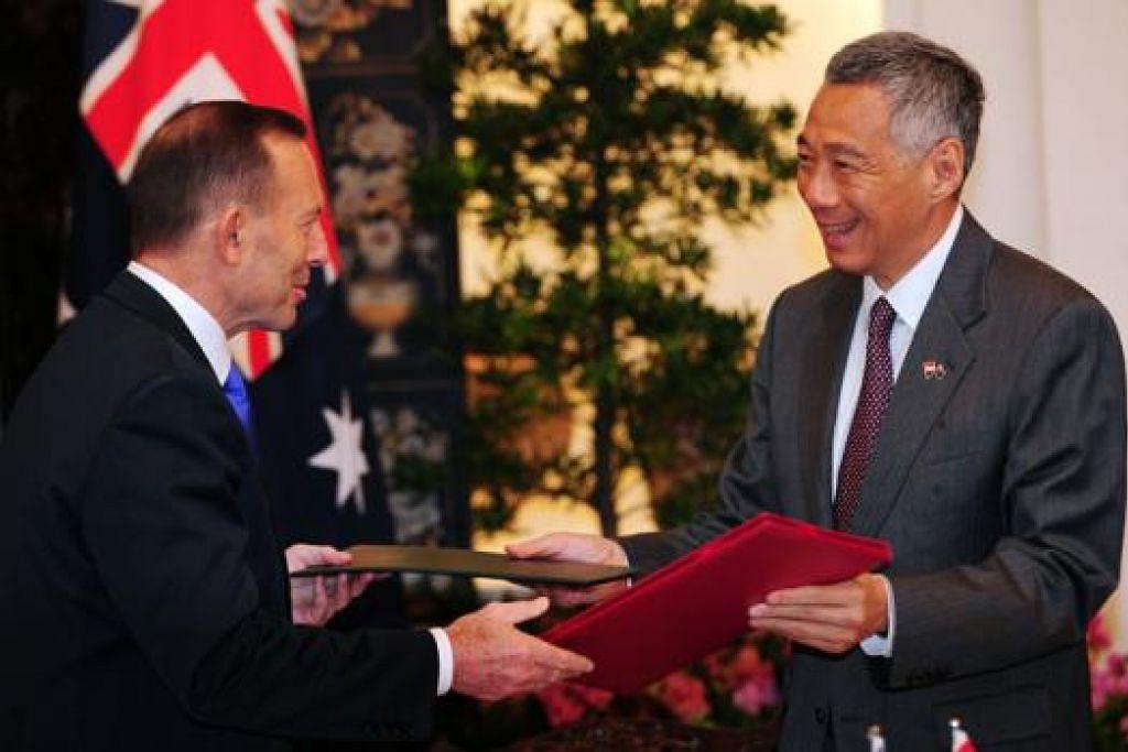 PERTINGKAT HUBUNGAN: (Dari kiri) Encik Abbott dan Encik Lee bertukar dokumen selepas memeterai Kerjasama Strategik Menyeluruh yang akan memperluas usaha sama antara Singapura dan Australia. - Foto AFP