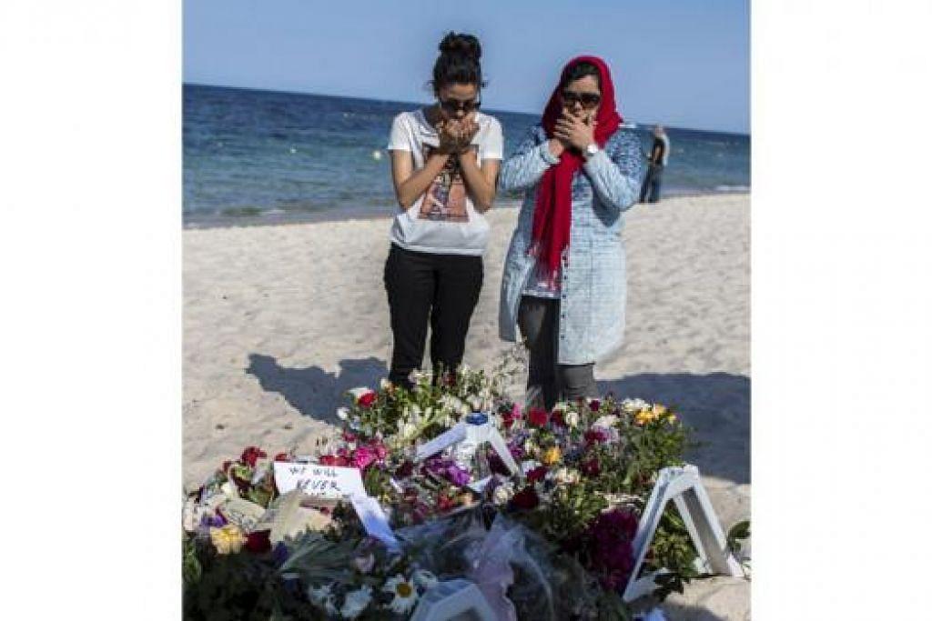 PERINGATI KORBAN: Dua wanita ini dilihat memanjatkan doa dekat kalungan bunga yang diletakkan bagi memperingati mereka yang terkorban dalam serangan pengganas di Sousse, Tunisia. - Foto REUTERS