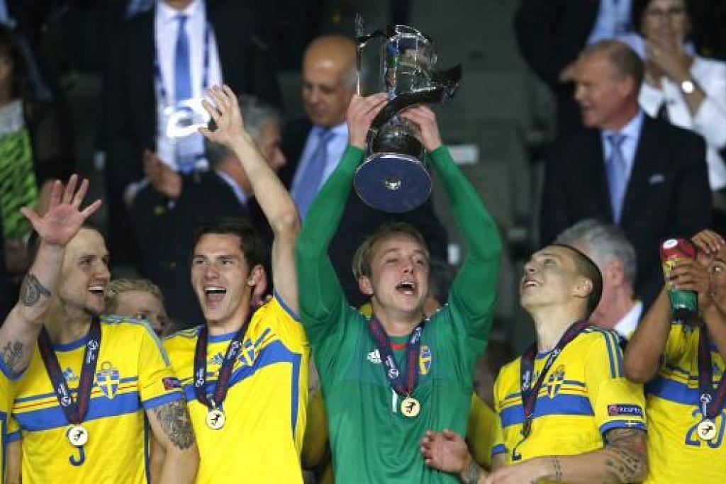 MAKHOTA DIJULANG: Penjaga gawang Sweden, Patrik Carlgren, menjulang trofi kejuaraan Euro Bawah 21 Tahun dengan diserta rakan-rakannya lain.
