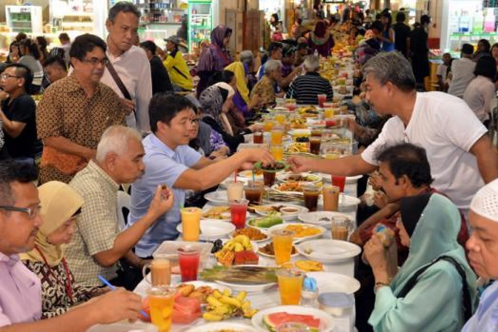 NIKMATI HIDANGAN BERBUKA: Encik Tan Chuan-Jin (duduk empat dari kiri) berbuka puasa bersama 200 warga memerlukan di Pasar Geylang Serai. - Foto M.O. SALLEH
