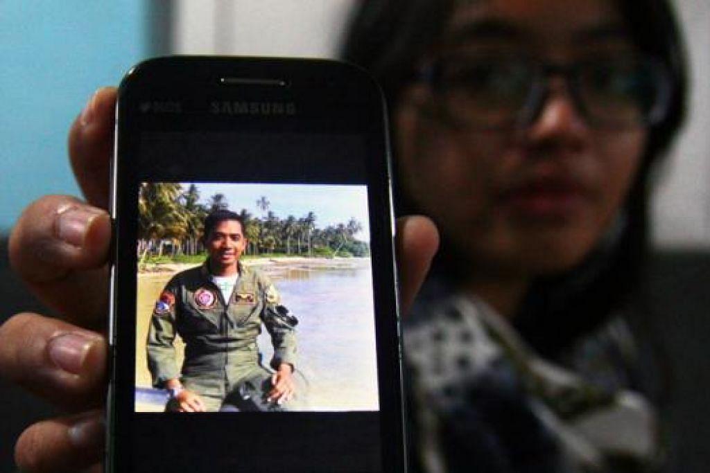HANYA TINGGAL KENANGAN: Seorang anggota keluarga menunjukkan gambar anggota Angkatan Udara Indonesia, Kapten Sandy Permana, yang terkorban dalam nahas kelmarin. - Foto AFP