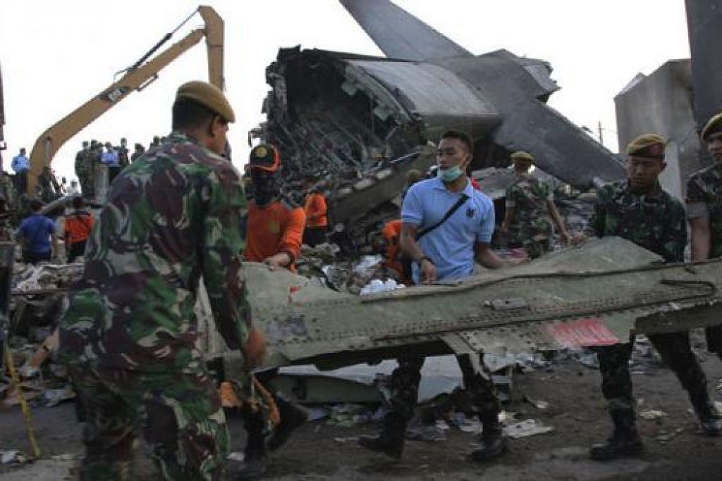 TIADA LAGI MANGSA DITEMUI: Para pekerja menyelamat mula membersihkan puing dan serpihan pesawat semalam. - Foto REUTERS