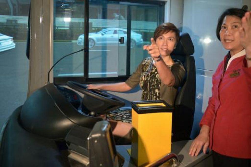 TEKNOLOGI CANGGIH: Cik Josephine Teo (kiri) cuba memandu menggunakan simulator kabin penuh dengan kapten bas Cik Amy Tan membantu beliau di Pusat Latihan dan Penilaian Bas SMRT semalam. - Foto SMRT