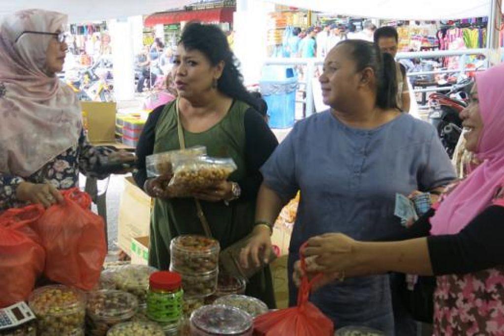 SANGAT BERBALOI BILA NILAI DOLAR MENINGKAT: Tiga beradik, (dari kiri) Cik Saadiah, Cik Azizah dan Cik Hetayah, membeli berbotol-botol kuih Raya daripada gerai Cik Anizah (kanan) di Pasar Larkin. - Foto AZAHAR MOHD