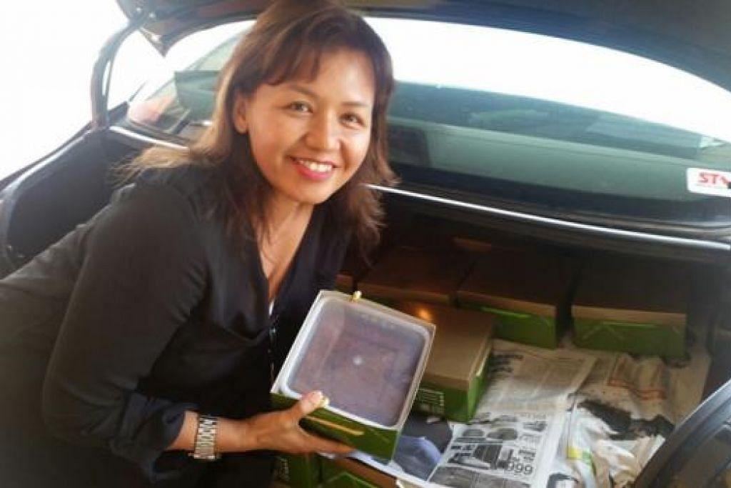 MASIH MURAH MESKIPUN HARGA SUDAH NAIK: Cik Riyan Ria memborong 150 kek kukus di Simpang Renggam untuk diagihkan sebagai cenderahati kepada para pelanggan dan kenalan. - Foto SAINI SALLEH