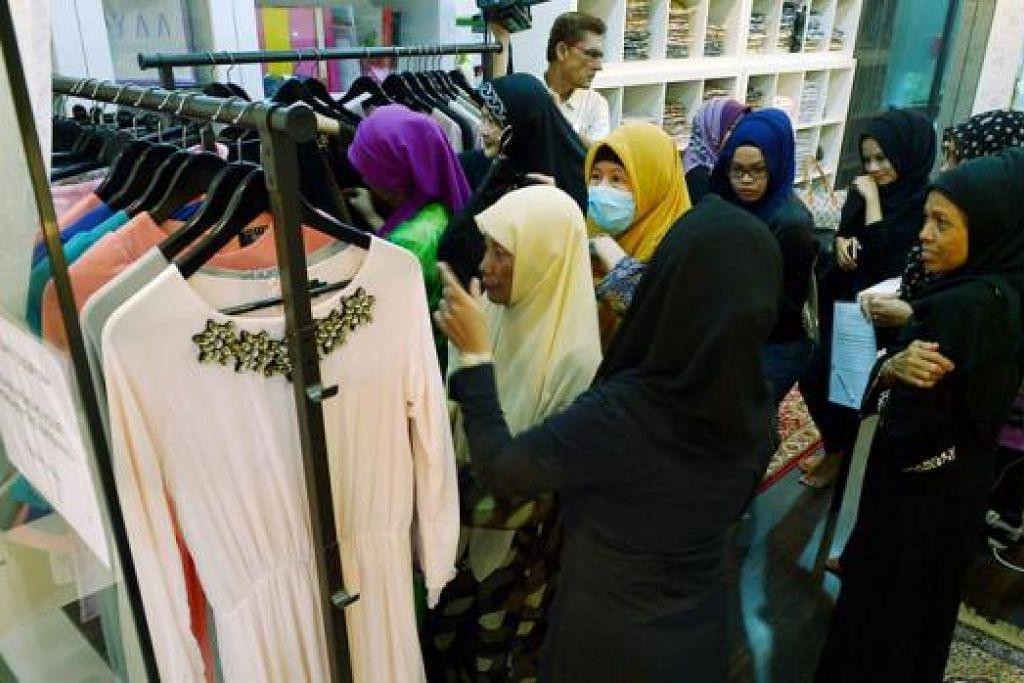 HADIAH RAYA: Pesakit barah buah dada dari Persatuan Ain menerima hadiah baju Muslimah chiffon Hari Raya daripada koleksi 'Enchanted Eid' di Sufyaa Boutique di Tanjong Katong Complex. - Foto TUKIMAN WARJI