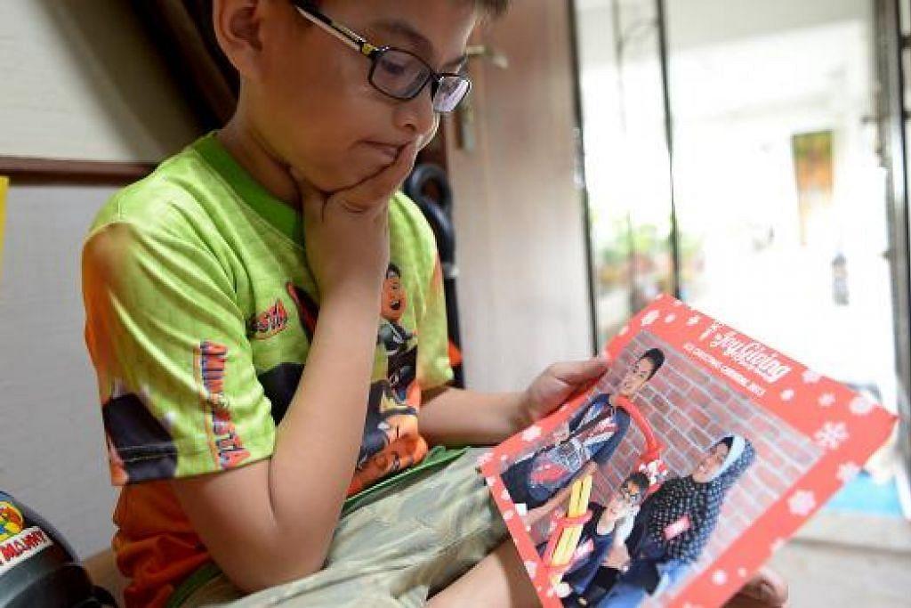 RINDU IBU: Muhammad Altamis sedih menatap gambar yang diambil bersama abang dan Allahyarhamha ibunya. Kanak-kanak berusia 10 tahun ini akan menyambut Syawal tanpa ibunya tahun ini. Beliau meninggal dunia Mei lalu akibat barah. - Foto TUKIMAN WARJI
