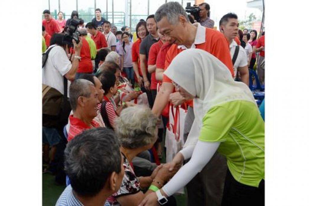 CENDERAHATI SG50: Encik Lee dan Dr Intan mula mengagihkan beg cenderahati Funpack kepada penduduk Jalan Kayu. Sebanyak 1.2 juta keluarga di Singapura akan menerima beg itu sempena sambutan SG50. - Foto TAUFIK A. KADER.