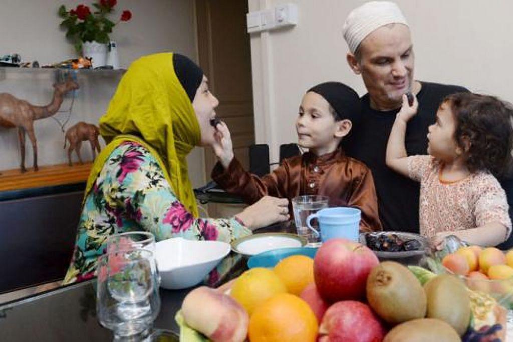IFTAR SIHAT: Encik Adnan dan isteri, Cik Salinah bersama dua anak mereka - Muhammad Ali, lima tahun, dan Nur Aliyah, dua tahun - biasanya berbuka puasa di rumah dengan makanan sihat sebelum pergi ke masjid menunaikan solat tarawih. - Foto TAUFIK A. KADER