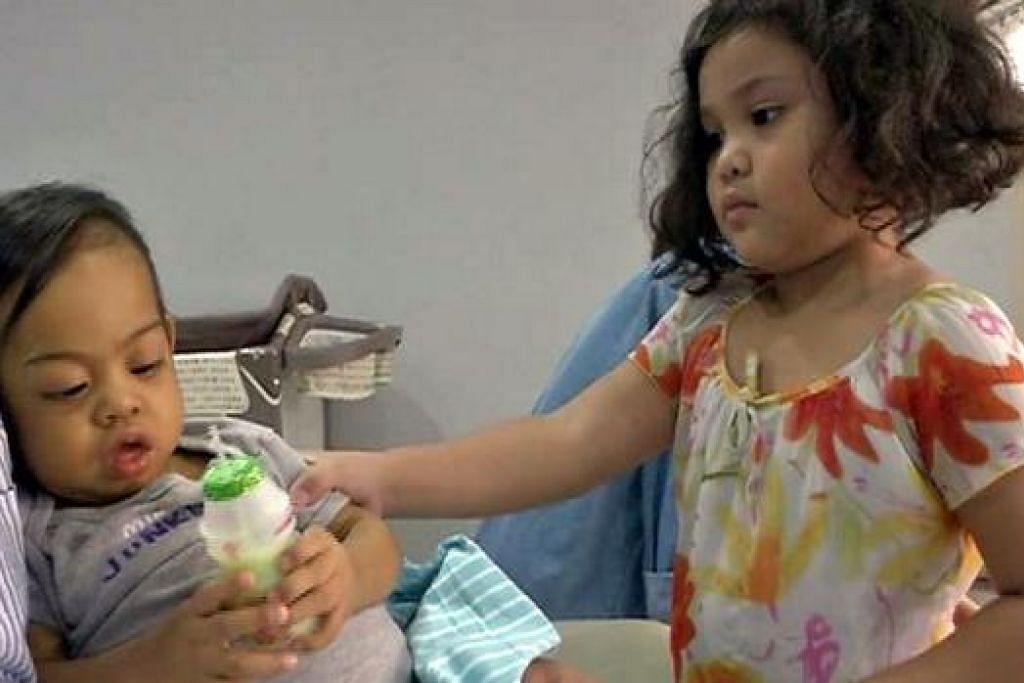 KASIHAN ADIKKU SAYANG: Arshad Imanshah Antashah (kiri), yang menghidap penyakit hati kronik 'biliary atresia' tahap ketiga, dibelai penuh kasih sayang oleh kakaknya, Rania Imelda Antashah, yang berusia lima tahun, di rumah mereka sekitar Selangor. - Foto ANTASHAH MOHD NOR