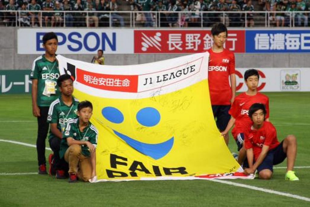 PENGALAMAN LUAR BIASA: Tiga pemain Singapura (berbaju hijau, dari kiri) – Hamizan, Adam dan Elijah – memegang bendera Fifa bersama pemain bawah usia 14 tahun Jepun di hadapan lebih 15,000 penyokong di Stadium Alwin di Matsumoto. – Foto THE STRAITS TIMES