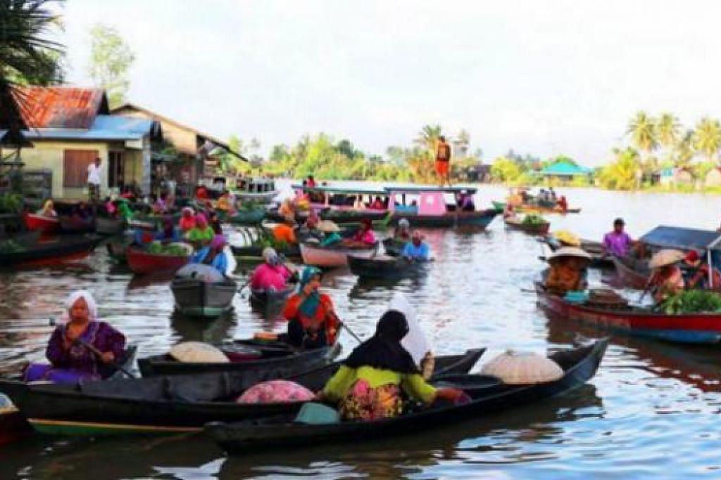 PASAR TERAPUNG: Kesibukan pasar terapung di kampungan Lokbaintain yang dipenuhi dengan peniaga yang berdagang buah-buahan, sayuran dan kuih-muih. - Foto-foto ASMAH MARICAN