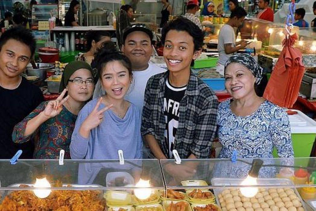 PENGALAMAN BEKERJA DI BAZAR RAMADAN: Dua wartawan Berita Harian, Anisa Abdullah (baju kelabu) dan Khairulameer Ramlan (baju kemeja corak kotak-kotak) bekerja sebagai peniaga sehari, menjual makanan ringan, memanggang kepak ayam dan membuat burger Ramly di gerai makanan di Geylang Serai yang dimiliki Cik Sabariah A. Razak (kanan), - Foto-foto KHALID BABA