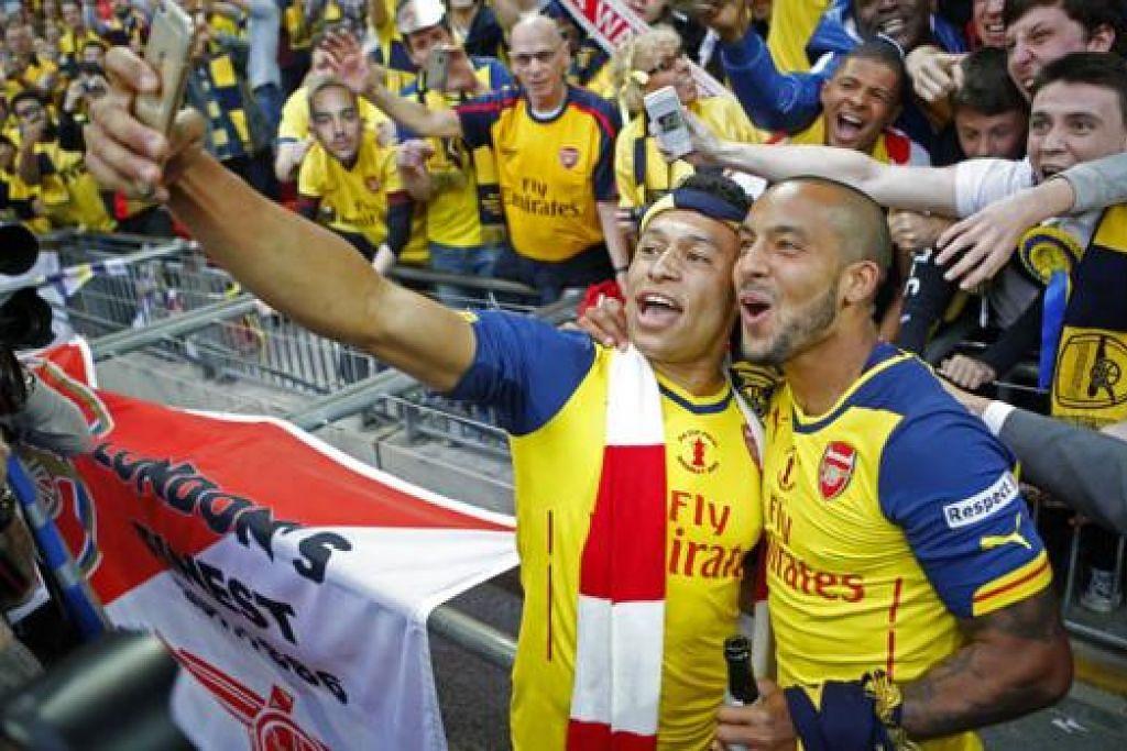 PERLU TERUSKAN KEJAYAAN: Alex Oxlade Chamberlain (kiri) dan Theo Walcott bergambar dengan penyokong selepas memenangi Piala FA musim lalu. - Foto REUTERS