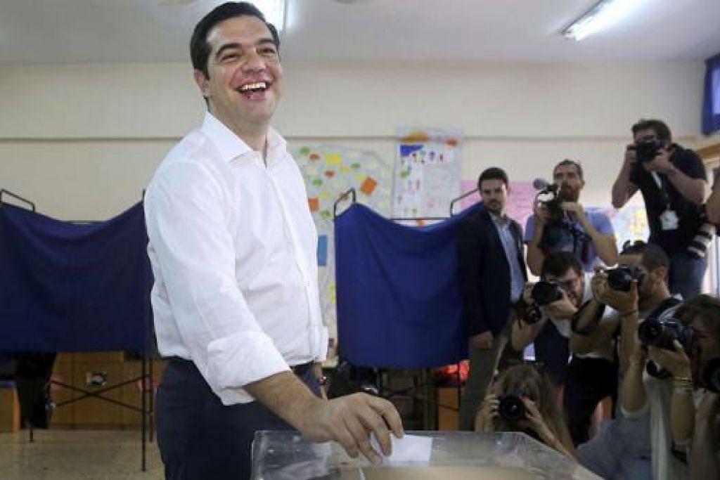 RAKYAT YANG BAKAL MENENTUKAN: Perdana Menteri Greece, Encik Alexis Tsipras, semalam membuang undi di sebuah pusat mengundi di Athens. - Foto REUTERS