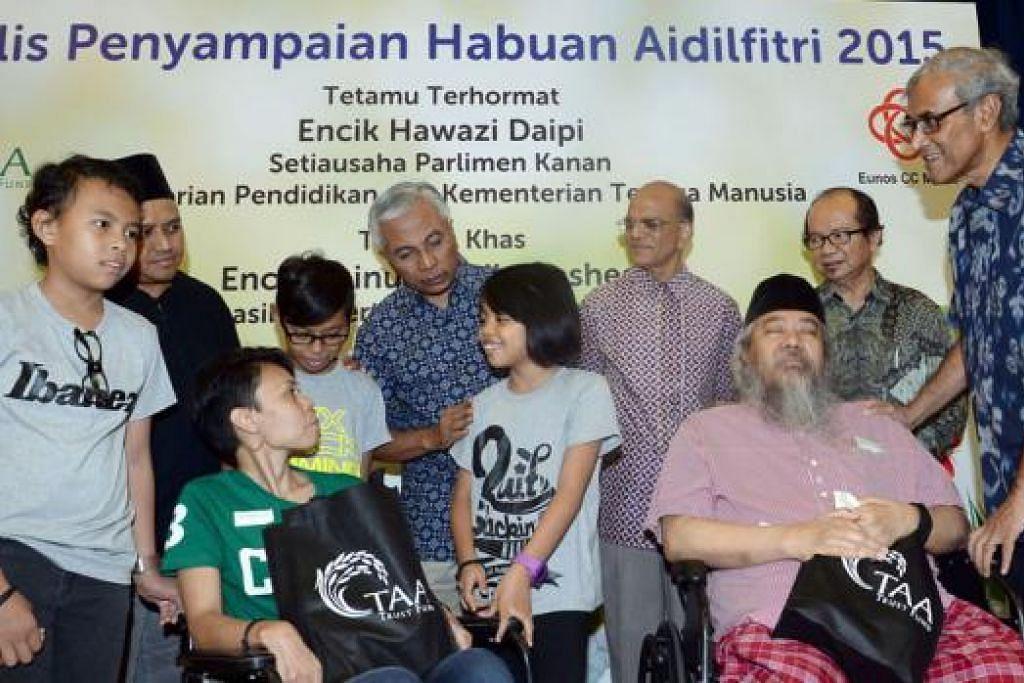 TERHARU MENERIMA HABUAN: Cik Halinah Yatim (berkerusi roda, berbaju hijau) bersama anak-anaknya (kesemua berbaju kelabu, dari kiri) Nur Syazlyana, Md Syahrizan dan Nur Syaheera serta Encik Mokhtar Ali (berkerusi roda, berbaju merah jambu) merupakan antara 325 penerima Tabung Amal Aidilfitri. Bersama mereka (dua dari kiri) Encik Muhd Harmizan Abdul Hamid, Encik Hawazi Daipi, Encik Ameerali Abdeal , Encik Zulkifli Mohamed dan Encik Zainul Abidin Rasheed. - Foto TAUFIK A. KADER