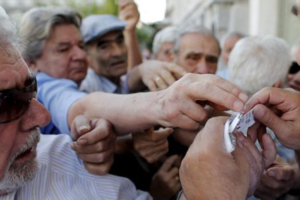 BEREBUT-REBUT: Golongan pencen diberi tiket beratur bagi memberi mereka keutamaan mengeluarkan wang pencen di bank setempat di Athens, kelmarin. - Foto REUTERS