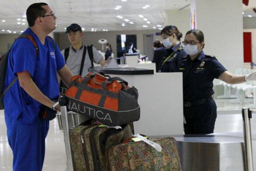 LANGKAH BERJAGA-JAGA: Pegawai kastam memakai pelitup muka ketika menunjuk arah laluan kepada penumpang yang tiba dari Korea Selatan di Lapangan Terbang Antarabangsa Ninoy Aquino. Filipina mengesahkan kes kedua Sindrom Pernafasan Timur Tengah (Mers).- Foto REUTERS.