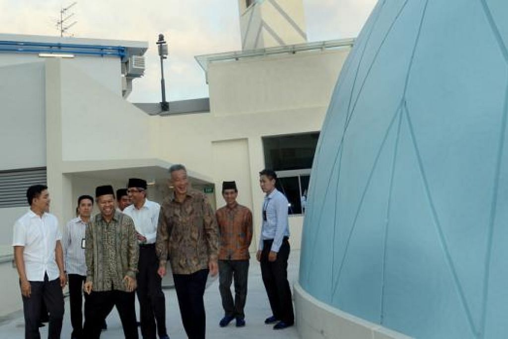 TINJAU MASJID: Encik Lee (tiga dari kanan) bersama Encik Tan (paling kiri); pengerusi Lembaga Pentadbir Masjid Al-Ansar, Encik Zahid Ahmad (depan, berbaju batik); Dr Yaacob (bersongkok, baju putih); dan Presiden Majlis Ugama Islam Singapura, Haji Alami Musa (dua dari kanan), meninjau bumbung Masjid Al-Ansar. - Foto TAUFIK A. KADER