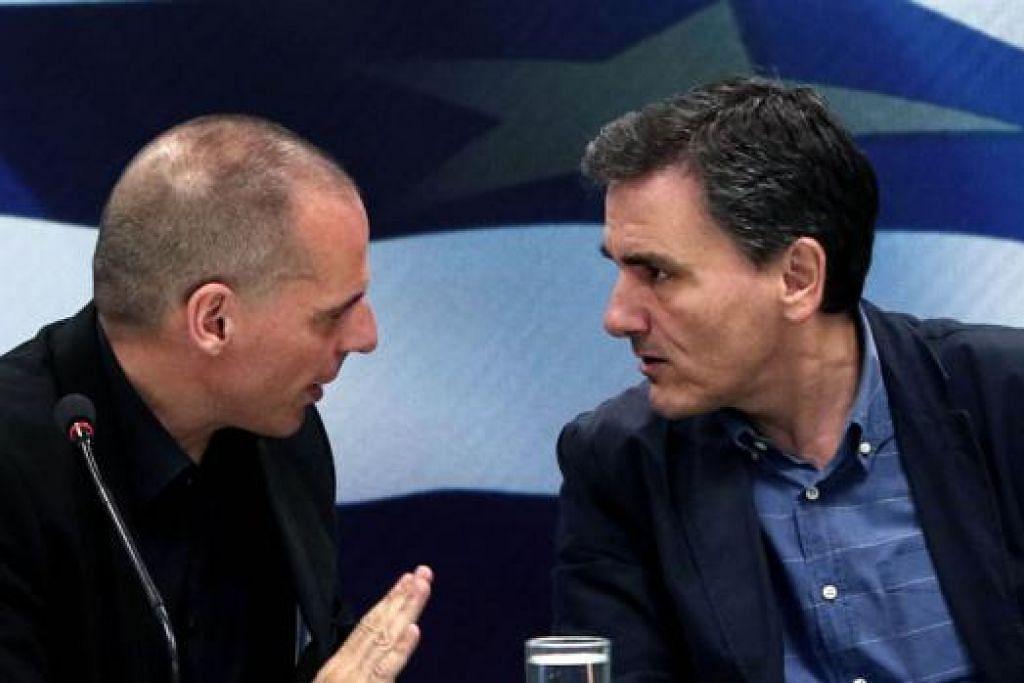 AMBIL ALIH TUGAS: Menteri Kewangan yang baru, Encik Tsakalotos (kanan), berbincang dengan Menteri Kewangan yang meletak jawatan, Encik Varoufakis, semasa upacara pengambilalihan di Athens, kelmarin. - Foto AFP