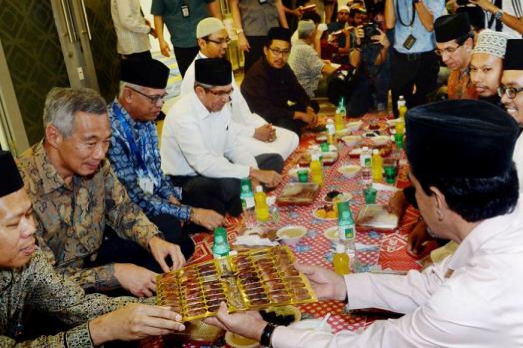 MAJLIS IFTAR: Encik Lee (dua dari kiri) menyertai jemaah Masjid Al-Ansar berbuka puasa. Awal dari itu beliau juga berpeluang meninjau kemudahan masjid dan beramah tamah dengan jemaah. - Foto TAUFIK A. KADER, MUIS