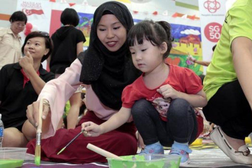 ARTIS VISUAL DAN PEREKA GRAFIK: Cik Amalina Ahmad bersama penduduk di kawasan Jurong West telah sama-sama menghasilkan karya seni 'Circle of Life'.  - Foto PASSION ARTS FESTIVAL 2015