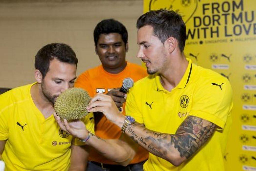 SEDAP TAK?: Penjaga gawang Borussia Dortmund, Roman Burki (kanan) kelihatan megajukan sebiji durian kepada pemain tengahnya, Gonzalo Castro (kiri), untuk dihidu. - Foto POLITEKNIK NANYANG