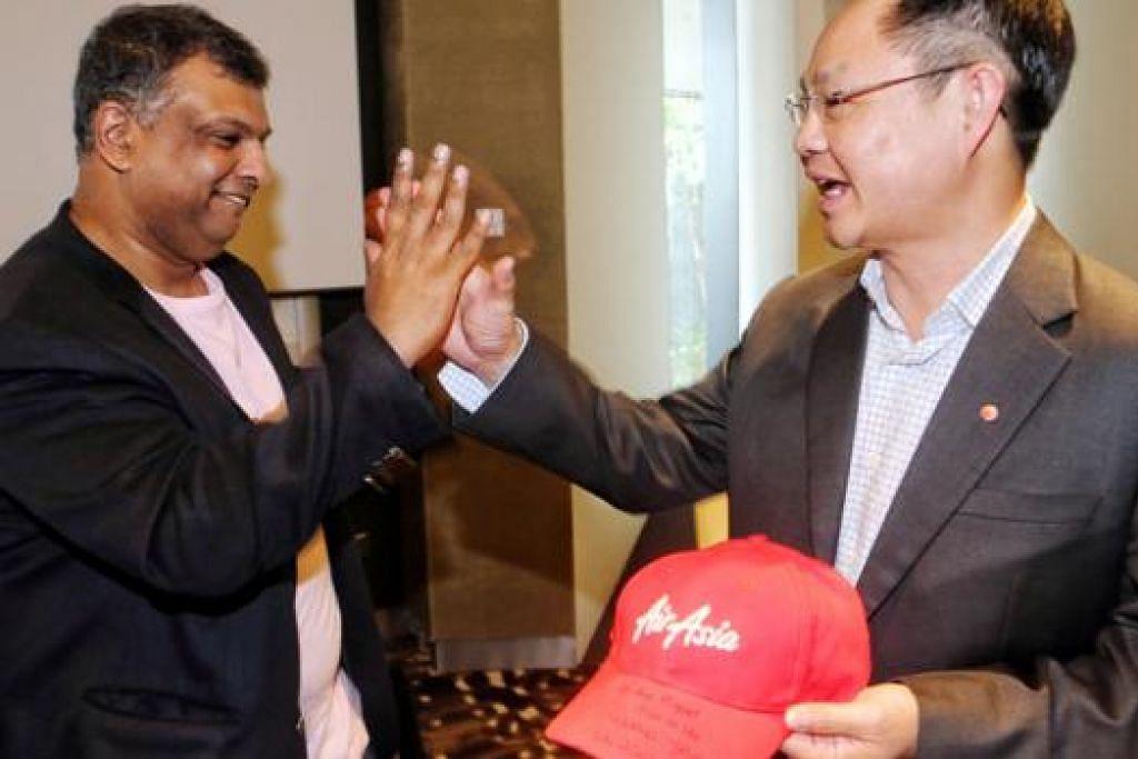 TAMBAT HATI AIRASIA: Encik Fernandes (kiri), yang memuji rekaan inovatif di T4, memberikan topi AirAsia kepada Encik Yam selepas sidang akhbar di Singapura semalam. - Foto ZAOBAO