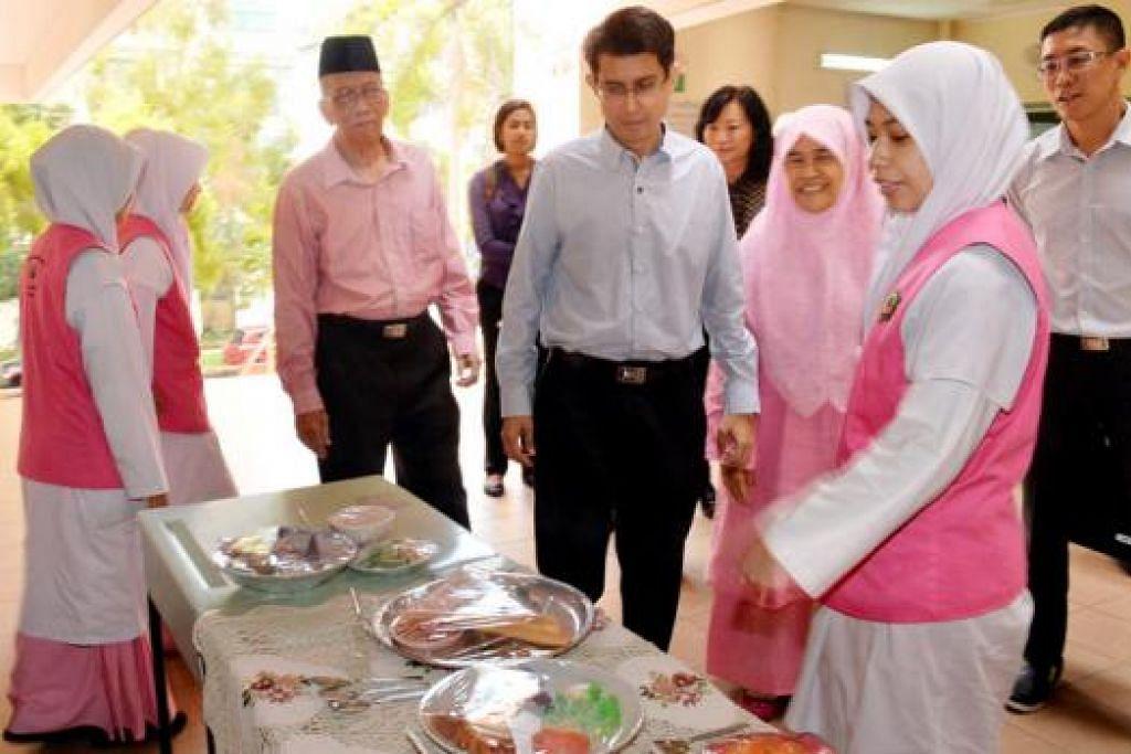 TAKLIMAT PEMAKANAN: Dr Faishal diberi taklimat mengenai beberapa jenis makanan tempatan yang boleh mempengaruhi kesihatan oleh Cik Lidiya Fathin Mustaffa, pelajar pra-universiti dua Madrasah Al-Ma'arif Al-Islamiah. – Foto M.O. SALLEH