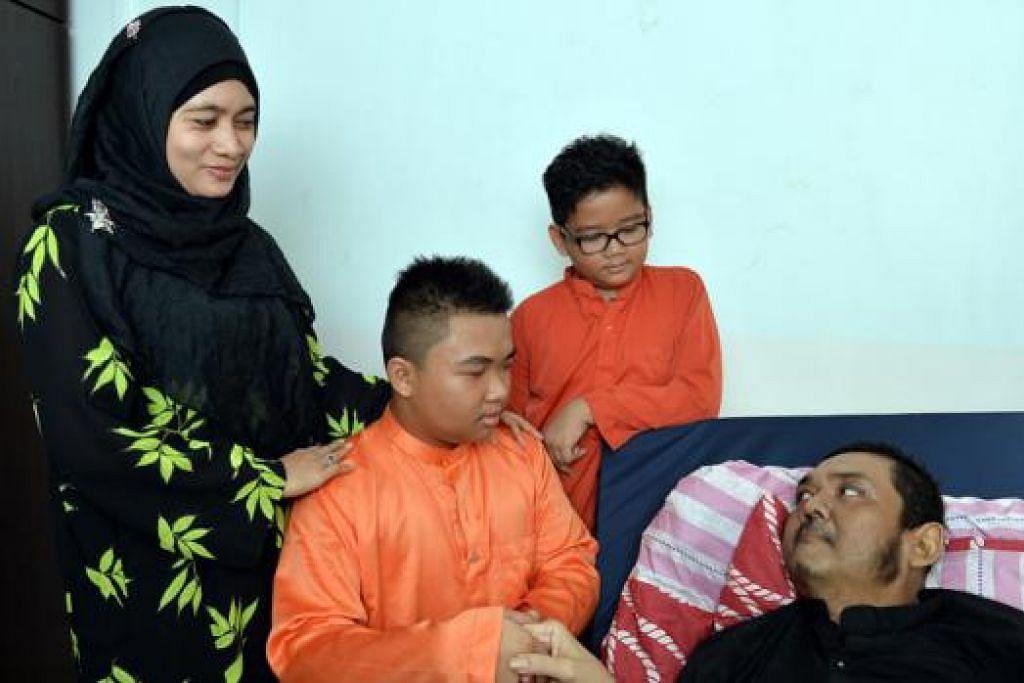 RAYA PENUH KESEDERHANAAN: Muhamad Hilmy Aqid, 15 tahun, bersalaman dengan bapanya, Encik Mohamad Khairi Abdul Dalif, seorang pesakit barah, sambil diperhatikan ibu tirinya, Cik Siti Rogayah Setapa, dan adiknya, Muhamad Zickey Zulkarnain, 13 tahun. - Foto M.O. SALLEH