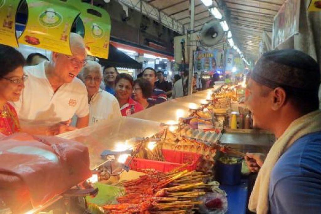 SUASANA MERIAH DI BAZAR: (Dari kiri) Dr Fatimah dan Encik Goh bertemu pegerai di bazar Ramadan. - Foto HAKIM YUSOF