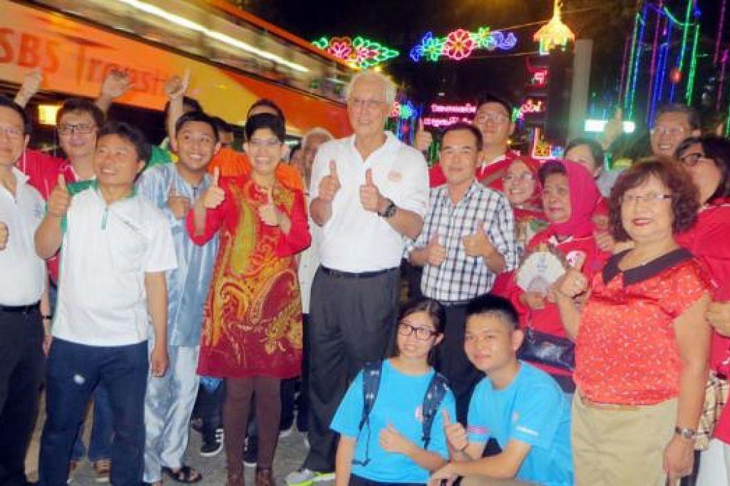 INGIN BAZAR DIPERLUASKAN: Encik Goh (tengah berbaju putih) dan Dr Fatimah (sebelah kanan Encik Goh) bergambar bersama sukarelawan Pasukan Ronda Bazar. - Foto HAKIM YUSOF